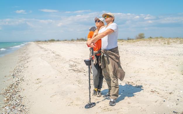 野生の海岸で金属探知機を備えた帽子をかぶった大人のカップル。仕事の前に彼らは海からの新鮮な風を感じるために立ち止まりました