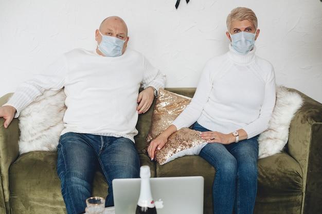 Взрослая пара в масках и белых свитерах сидит на диване и использует ноутбук для видеозвонка дома