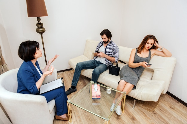 Adult couple is sitting and looking at their phones. they are bored. people don't listen to therapist. doctor is trying to talk to them and showig that with her hands.