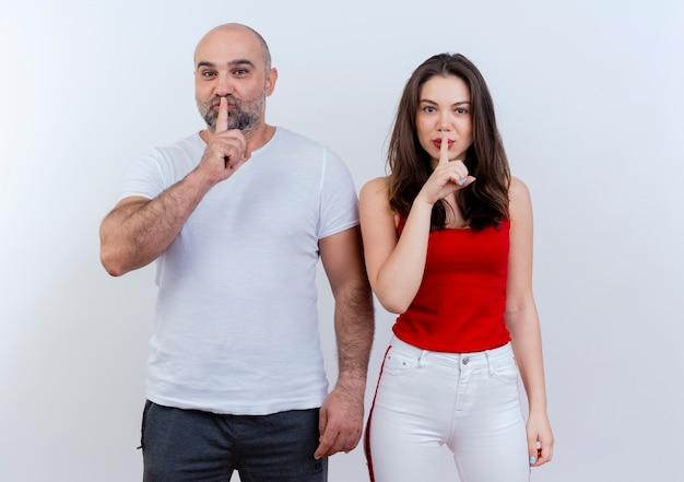 Взрослая пара смотрит и делает жест молчания