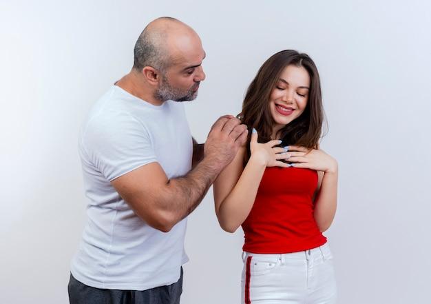 Взрослый мужчина пара кладет руки на плечо женщины, глядя на ее женщину, касающуюся ее груди, улыбаясь и глядя вниз