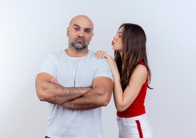Coppia adulta uomo in piedi con postura chiusa cercando donna che mette le mani sulla spalla guardandolo e facendo gesto di bacio