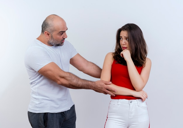 Adult couple man touching woman's arm telling her something and unpleased woman touching chin both looking at each other