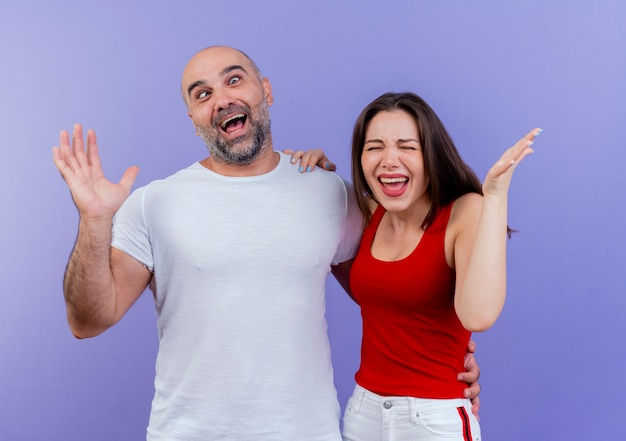 Adult couple playful man showing empty hand with crossed eyes and annoyed woman putting hand on his shoulder and showing empty hand with closed eyes