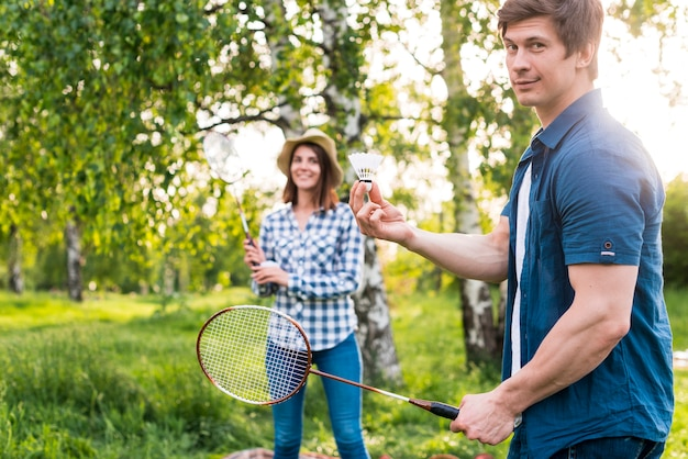Adult couple playing badminton in park