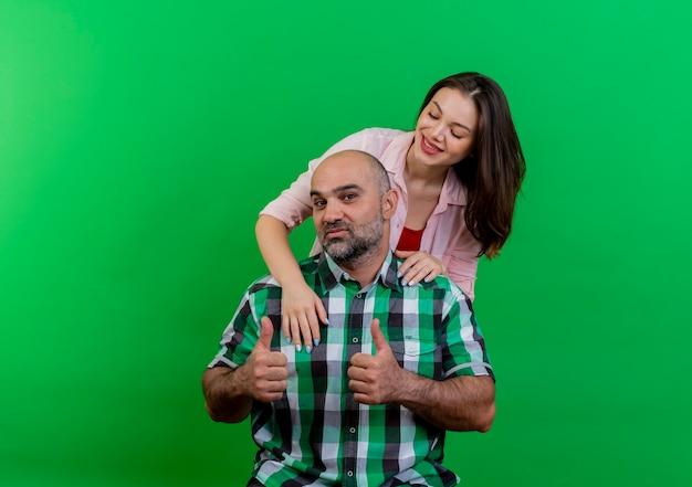 Взрослая пара довольна женщина, стоящая за мужчиной, положив руки ему на плечи, глядя на него, и уверенный в себе мужчина, смотрящий, показывает палец вверх