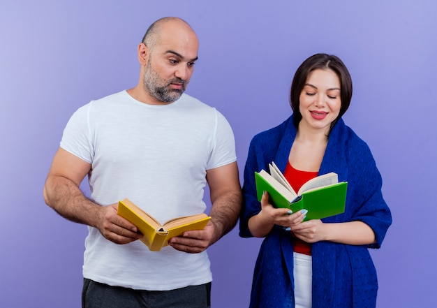 Adult couple pleased woman wrapped in shawl reading book impressed man holding book and looking at her book