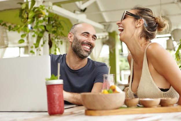 Взрослая пара отдыхает в кафе на тротуаре, пьет смузи, оживленно разговаривает и использует ноутбук.