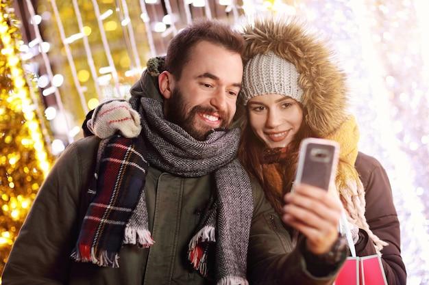 Взрослая пара делает покупки в городе во время рождества