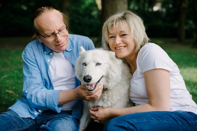 Взрослая пара сидит на траве с белой собакой