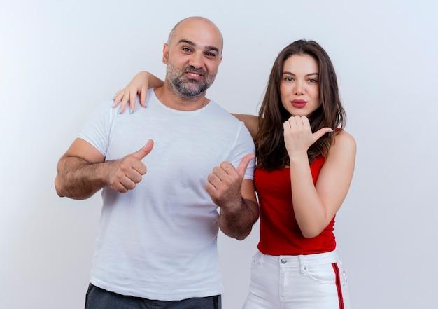 Взрослая пара улыбается мужчина показывает палец вверх и уверенная в себе женщина кладет руку ему на плечо и указывая на сторону