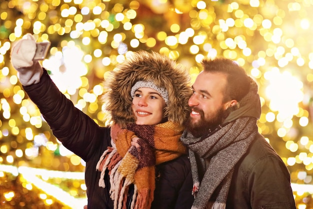 Adult couple taking selfie in the city during christmas time