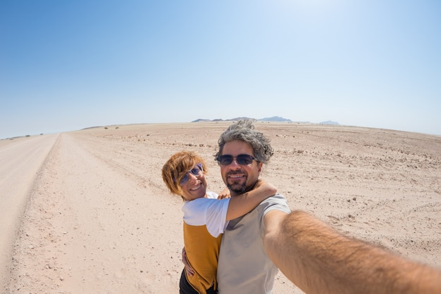 Adult couple taking selfie on gravel road in the namib desert, namib naukluft national park, main travel destination in namibia, africa