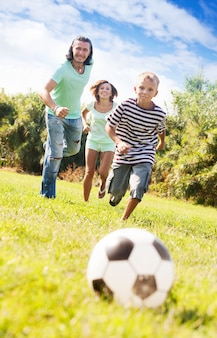 Adult couple and teenager playing with soccer ball