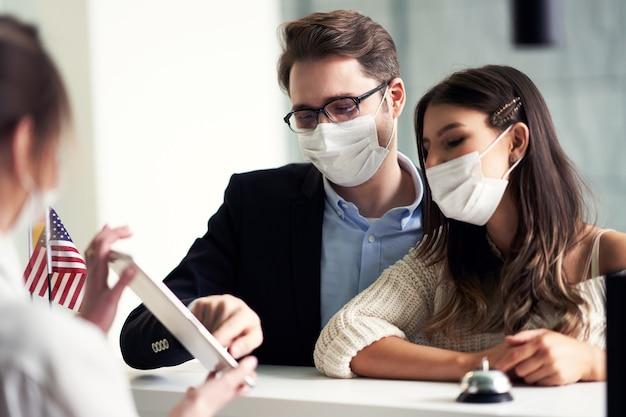 Covid-19制限のためにマスクを着用している大人のカップルがホテルにチェックイン