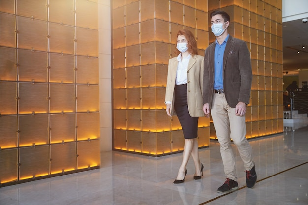 Adult couple wearing medical masks while walking along the hall of an office building. website banner