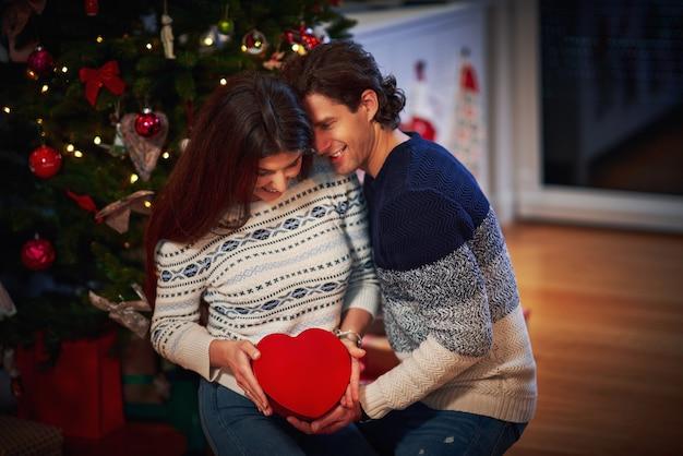 クリスマスツリーの上のプレゼントと大人のカップル Premium写真