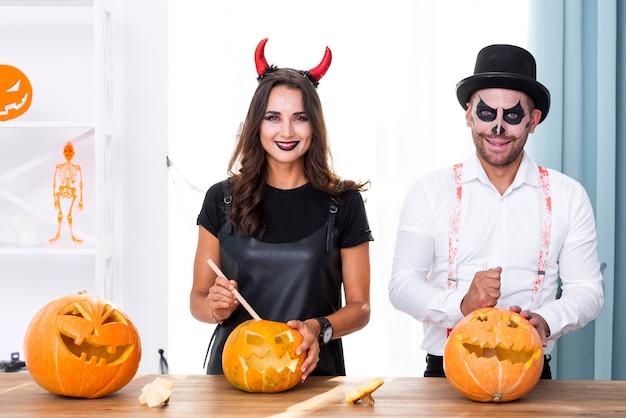 Взрослая пара с тыквами на хэллоуин