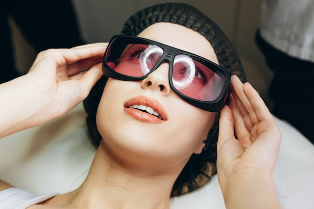 Adult cute woman having laser hair removal in professional beauty salon. close up.