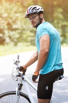 Взрослый велосипедист, стоящий на дороге