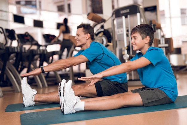 Adult dad and boy doing stretching in the gym.