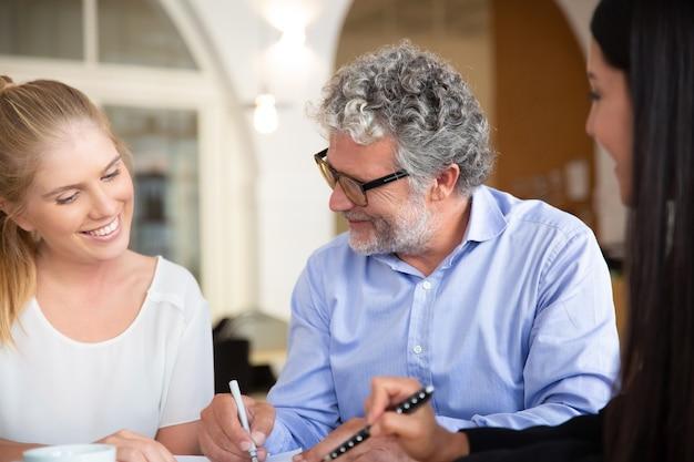 大人の娘と成熟した父親がエージェントと会い、保険契約に署名