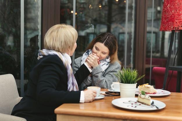 大人の娘が母親の手にキスして微笑む