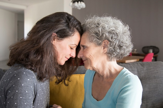 Adult daughter and old mother touching foreheads