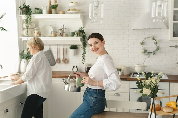 大人の娘がティーポットからマグカップにお茶を注ぐ一方で、高齢の母親が皿を洗う