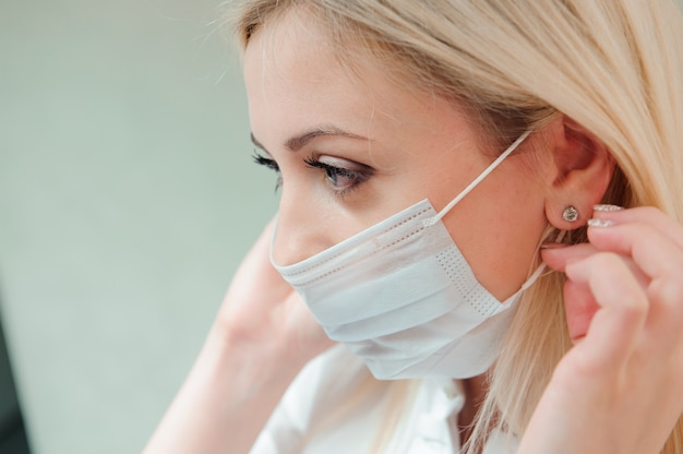 Adult dentist puts a protective mask on her mouth.