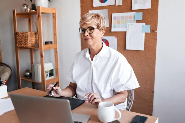 Взрослый дизайнер работает с ноутбуком в своем офисе