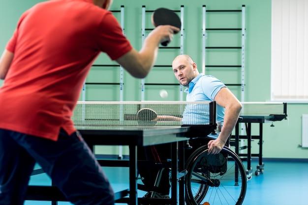 Взрослый человек-инвалид в инвалидной коляске играет в настольный теннис со своим тренером
