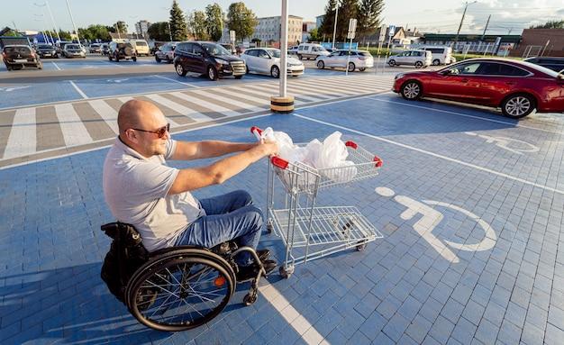 車椅子の成人障害者がスーパーマーケットの駐車場で車に向かってカートを押す