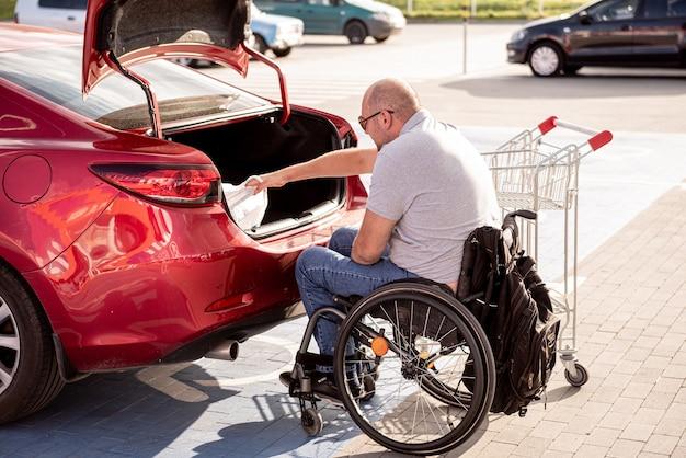 휠체어를 탄 성인 장애인은 슈퍼마켓 주차장에 있는 차 트렁크에 물건을 싣는다