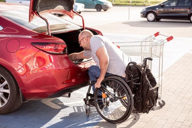 車椅子の成人障害者がスーパーマーケットの駐車場で車のトランクに買い物をする Premium写真