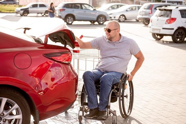 車椅子の成人障害者がスーパーマーケットの駐車場で車のトランクに買い物をする