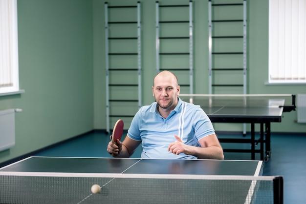 Взрослый человек-инвалид на тренировке в инвалидной коляске перед игрой в настольный теннис