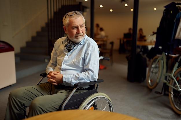 Взрослый человек-инвалид в инвалидной коляске, инвалидность, интерьер кафетерия на фоне. инвалиды пожилого возраста, парализованные люди в общественных местах