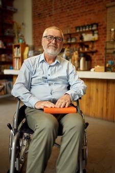 Взрослый инвалид в инвалидной коляске держит книгу