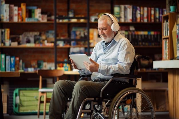 Взрослый человек-инвалид в инвалидной коляске слушает музыку в наушниках, инвалидности, интерьере кафетерия на заднем плане. инвалиды пожилого возраста, парализованные люди в общественных местах