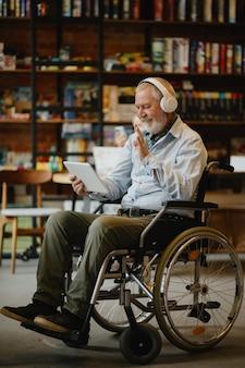 Взрослый инвалид в инвалидной коляске слушает музыку