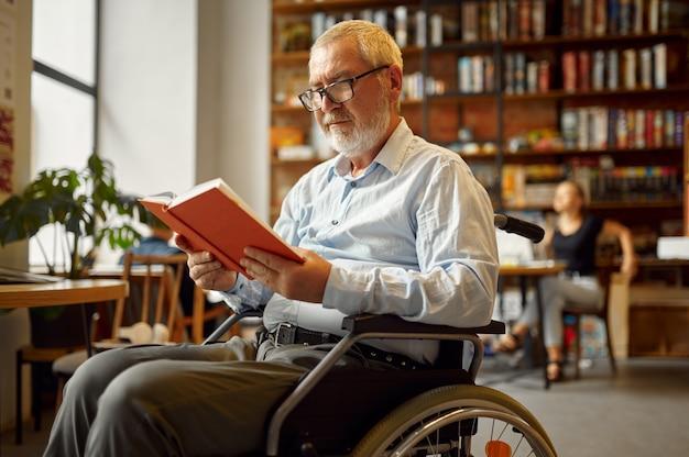 Взрослый человек-инвалид в инвалидной коляске, читая книгу, инвалидность, книжную полку и интерьер университетской библиотеки на заднем плане. люди старшего возраста с ограниченными возможностями, парализованные люди получают знания