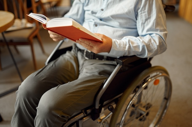Взрослый человек-инвалид в инвалидной коляске, читая книгу, инвалидность, книжную полку и интерьер университетской библиотеки на заднем плане. инвалиды пожилого возраста, парализованные люди