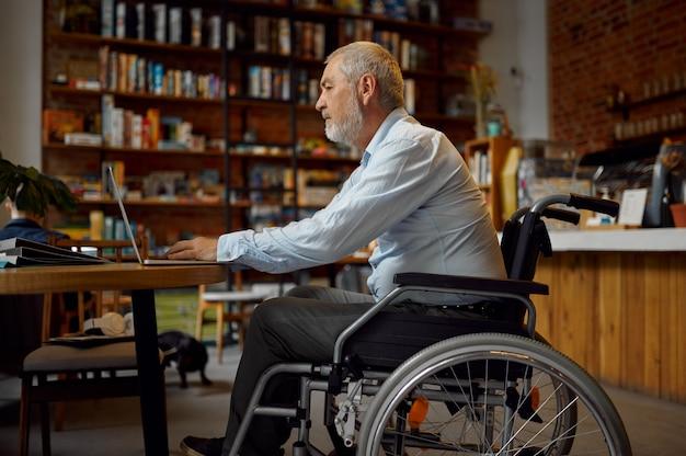 Взрослый человек-инвалид в инвалидной коляске, использующий ноутбук, вид сверху, инвалидность, книжную полку и интерьер университетской библиотеки на заднем плане. люди старшего возраста с ограниченными возможностями, парализованные люди получают знания