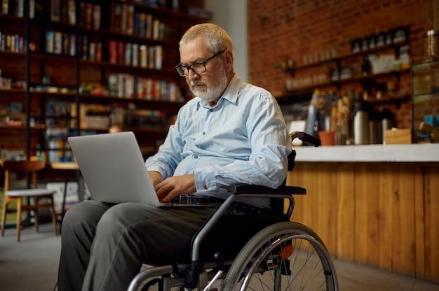 Взрослый человек-инвалид в инвалидной коляске с помощью ноутбука