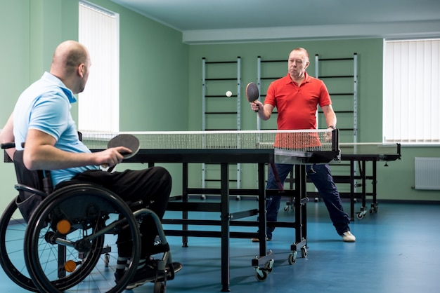 Adult disabled man in a wheelchair play at table tennis with his coach
