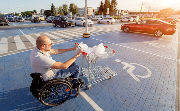 Adult disabled man in a wheelchair pushes a cart towards a car in a supermarket parking lot