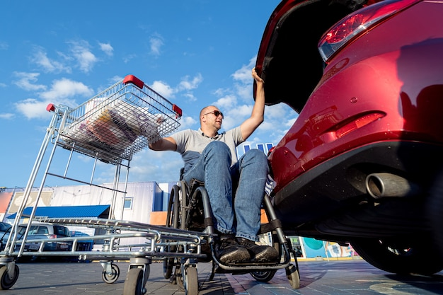 Adult disabled man in a wheelchair puts purchases in the trunk of a car in a supermarket parking lot