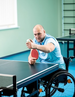Adult disabled man in a wheelchair training before play at table tennis