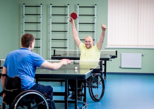 탁구를 재생하는 휠체어에 성인 장애인 남자